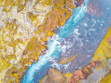 Hraunfossar series of waterfalls barnafoss aerial image of turquoise water streaming down gaps in lava collecting in plunge pools Stock Photo