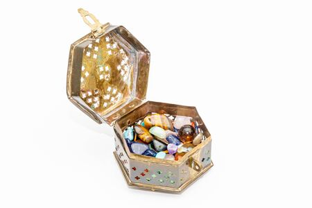 Old small jewel box open and full of colorful stones