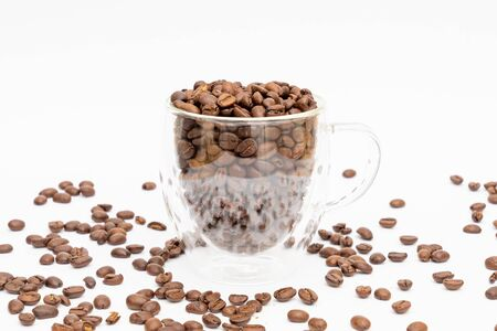 Glass thermos insulating cup transparent filled with roasted coffee beans on a white underground