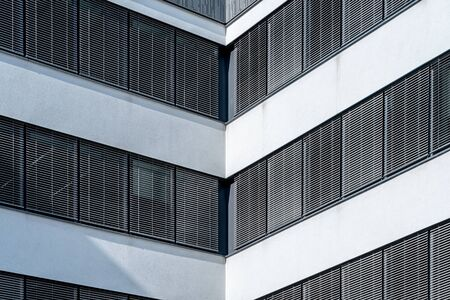 Modern facade front of modern business office building with dark window shades and white elements