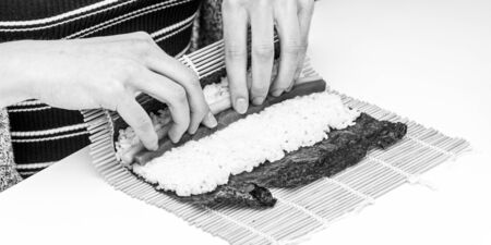 Sushi roll Japanese dish tuna cucumber preparing ingredients rolled in algae sheet in black and white