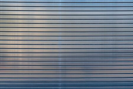 Stainless steel overhead door reflecting midday sunlight pattern