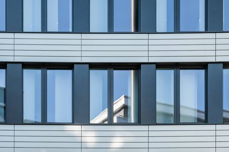 Modern facade of office buildings with stainless steel elements and reflecting big windows