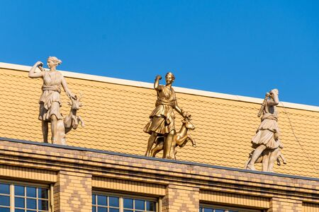Golden statue of Diana besides marble statues on top of yellow brick facade with patterns
