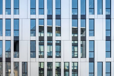 Modern office building reflecting in facade of stainless steel and mirrored glass windows