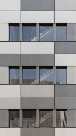 Modern facade front of modern business office building with stainless steel cladding in different grey colors Stockfoto