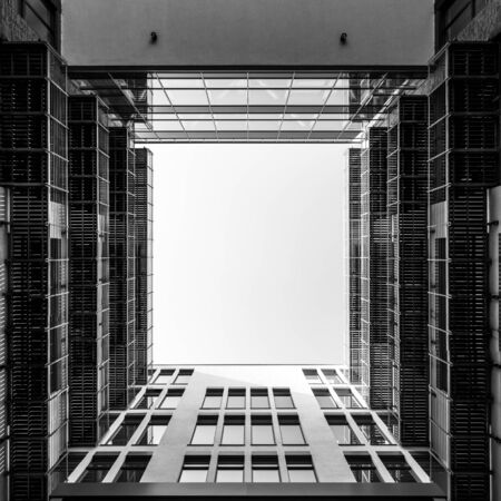 Inner yard of modern office building looking upwards through square opening into the sky in black and white