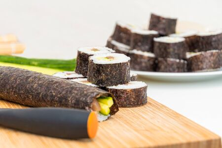 Sushi roll Japanese dish rolls ingredients and knife on bamboo kitchen board Stockfoto