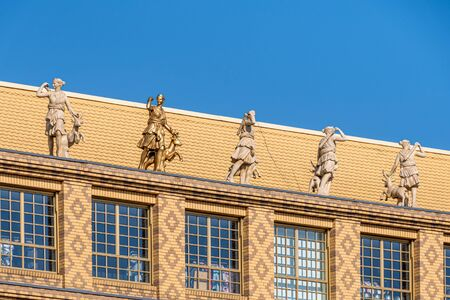 Golden statue besides marble statues on top of yellow brick facade with patterns and big windows