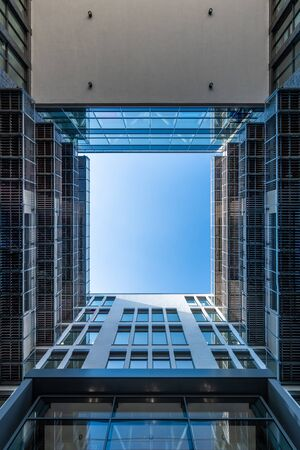 Inner yard of modern office building looking upwards along modern facade into the blue sky Stockfoto