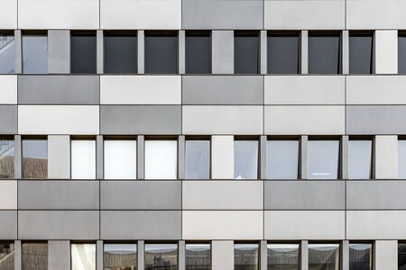 Modern facade front of modern business office building with stainless steel cladding in different grey tones