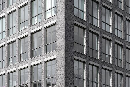 Modern facade of office building with dark bricks and high windows Stockfoto