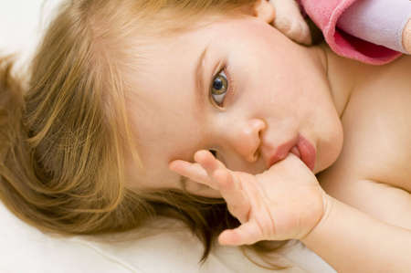 Beautiful baby girl sucking her thumb and hugging her doll in cot just before bedtime Stock Photo - 4202005