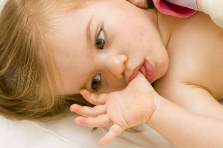 suck: Beautiful baby girl sucking her thumb and hugging her doll in cot just before bedtime