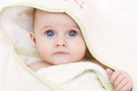 baby girl wrapped in a white towel after bathtime photo