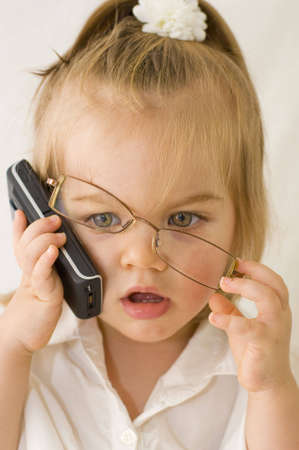 phone professional: Baby girl dressed up in business attire wearing glasses and talking with mobile phone