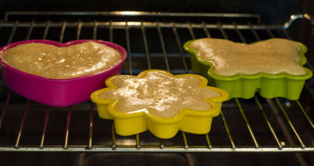 mini oven: Mini cakes in coloured silicone moulds baking in the oven