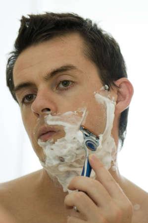hombre afeitandose: De afeitar joven en la ma�ana mirando en el espejo de