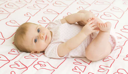 bedspread: Baby girl playing with her feet on a heart themed bedspread