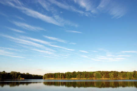 Bright blue cloudy sky over pond surrounded by colorful trees Stock Photo