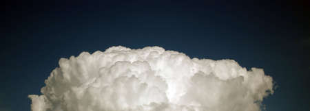Giant cotton-like cloud in the dark blue sky Stock Photo