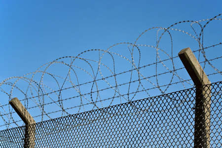 Fence with barbwire over blue sky Stock Photo