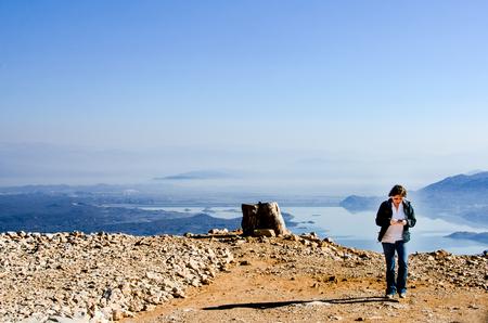 Woman is walking from the edge of lake Slansko in Montenegro