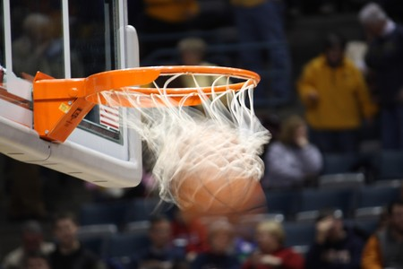 basketball shot: Basket ball going through the rim and net to complete the shot.