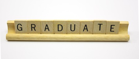 jumble: Wooden tile letters spell out Graduate word.