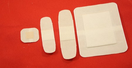 Four bandages isolated on a red background.