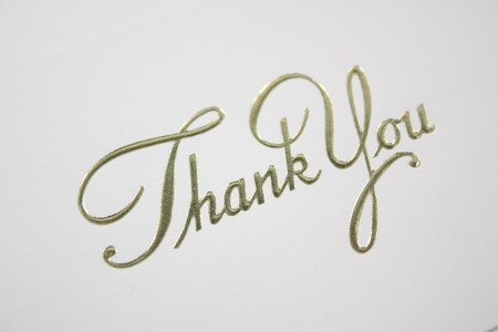 Thank you written in cursive on a card cover.