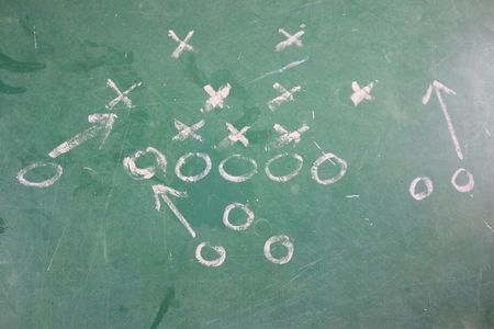 Football play diagramed out on a chalkboard. Imagens