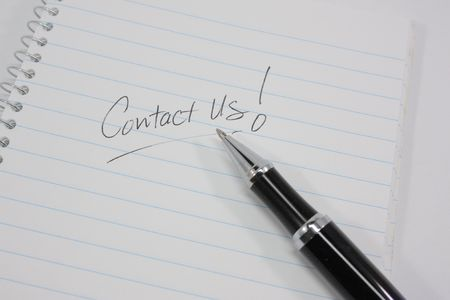 Contact us written on a notebook with a pen.