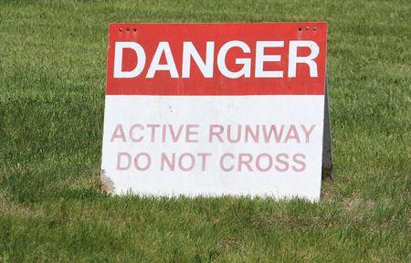 danger: Danger active runway sign on the grass.