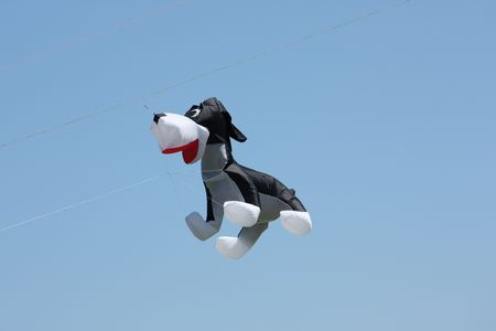 A huge kite in the shape of a dog against a blue sky.