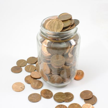 pennies: A jar full of U.S. Pennies isolated on white.
