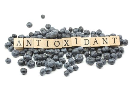antioxidant: Blueberries on a white background with Antioxidant spelled out in wooden blocks.