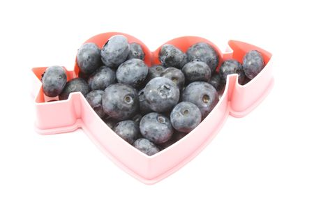 Blue berries in a heart shaped form showing healthiness.