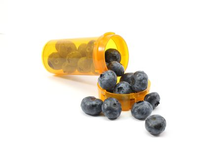 Blue berries spilling out of a prescription rx bottle.