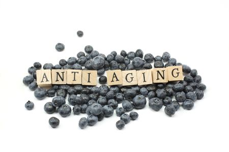 aging: Anti Aging wooden blocks on blue berries. Stock Photo