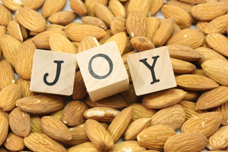 A background of almonds with the word Joy in wood blocks. photo