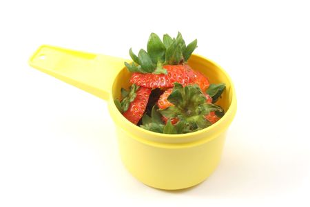 Tops of strawberries cut off and placed in a yellow measuring cup displayed on a white background
