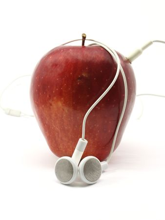Red Delicious apple wrapped in music earbuds photographed on a white background Stock Photo - 5386349