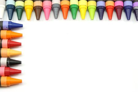 Crayons lined in a row to make a border around the edge of screen photographed on a white background Stock Photo