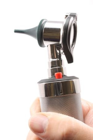 otoscope: Up close photograph of otoscope held in a mans hand