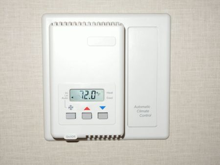 An electric thermostat set at 72 degrees on a wall.