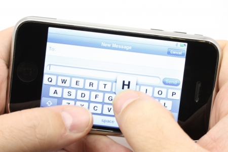 sms: Texting on a touch screen phone turned sideways.