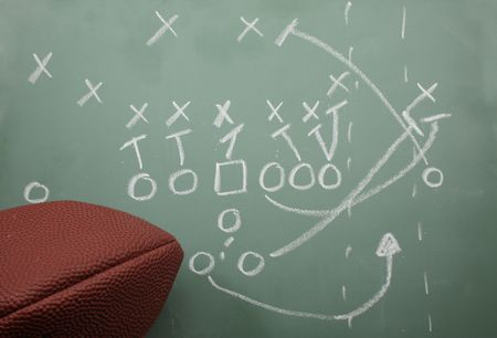 Football sweep play diagram on a chalk board with a football.
