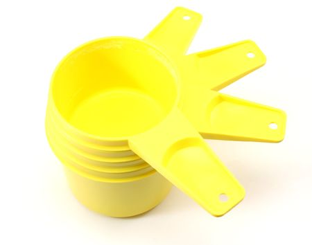 Yellow plastic measuring cups photographed on a white background