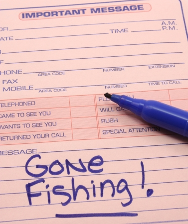 Gone Fishing on an Important Message pad with a blue pen.